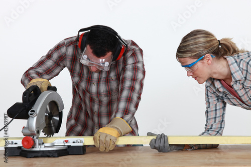Couple sawing timber