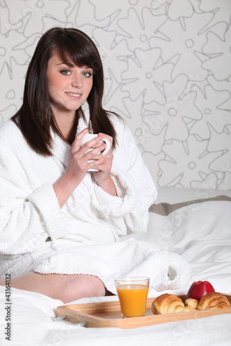 Woman in bathrobe with coffee in hand