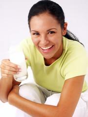Joven mujer latina bebiendo un vaso de leche.