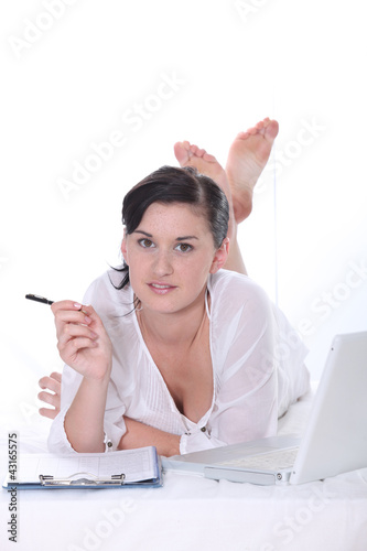 Young woman lying down with a laptop computer and clipboard