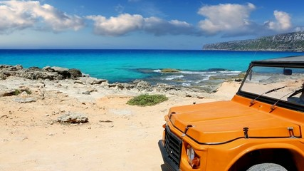 beautiful beach with convertible car in ibiza