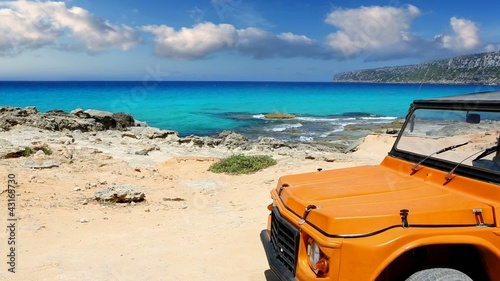 beautiful beach with convertible car in ibiza