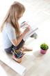 teenage girl sitting on floor drawing