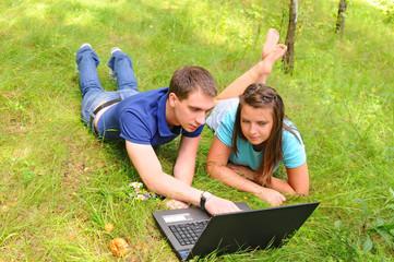 Молодые люди с ноутбуком на природе