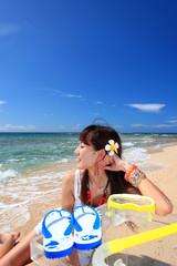 南国沖縄のビーチで寛ぐ女性