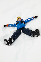 Young Boy Making Snow Angel On Slope