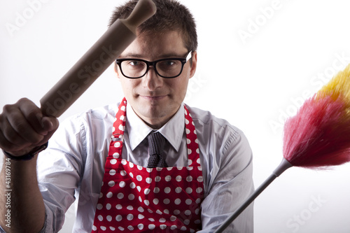 Young man with duster and kitchen tool
