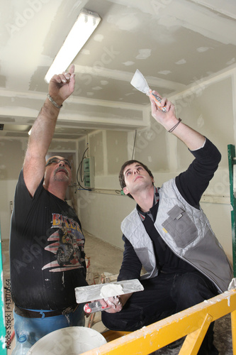 Two plasterers working together