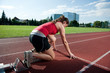 Female athlete in the starting block, getting ready to go
