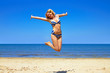 happy girl wearing bikini jumping on beach
