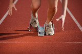 female sprinter leaving the starting blocks on a track