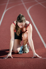 Young female sprinter on a running track,getting ready to go