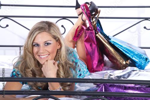 Junge Frau auf dem Bett lachend liegend nach Shopping