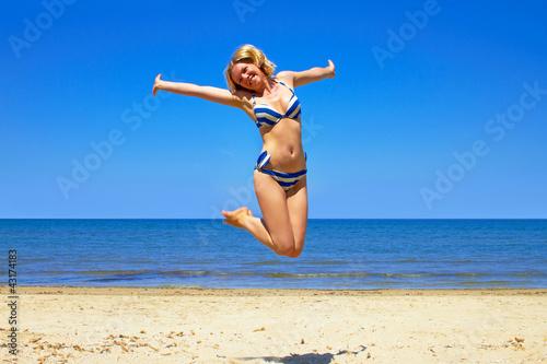 happy girl wearing bikini jumping on beach