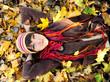 Girl lying in leaves.