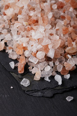 Coarse pink himalayan, sea salt on black slate stone background,