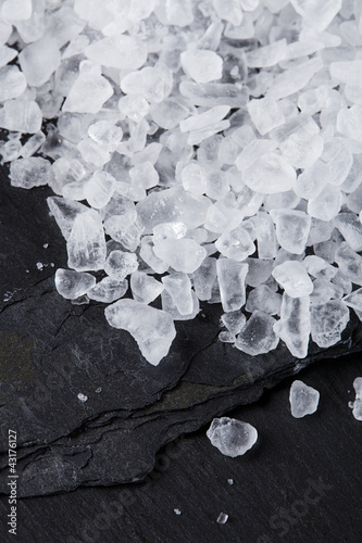Coarse sea salt on black slate stone background, closeup