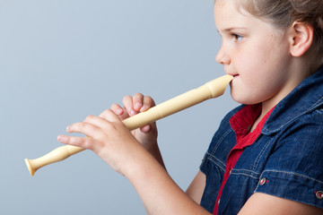 Little girl plays the flute on a grey background