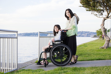 Taking care of sister in wheelchair by beach