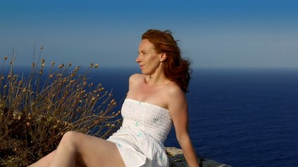 happy redhead woman  feeling wind in high cliff  sea