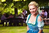 junge blonde Frau im Dirndl im Biergarten