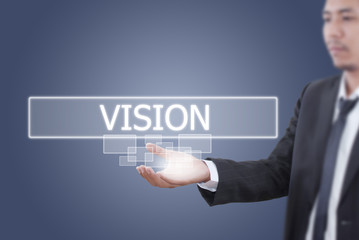 Businessman holding Vision word on the whiteboard.