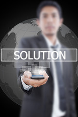 Businessman Holding mobile with Solution word.