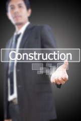 Businessman holding Construction word on the whiteboard.