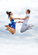 Portrait of a happy young couple jumping in air against sky.
