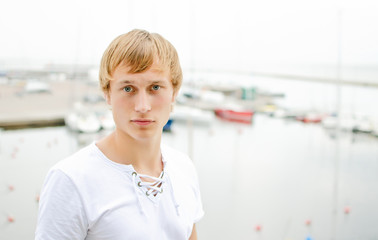 Handsome male portrait, against of the pier with yachts.
