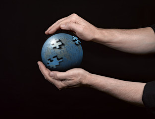Man holding a glowing earth globe in his hands.