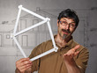 man with folding rule in the shape of a house