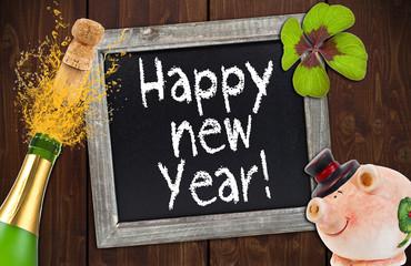Kreidetafel mit Sektflasche, Schwein, Kleeblatt auf Holzwand
