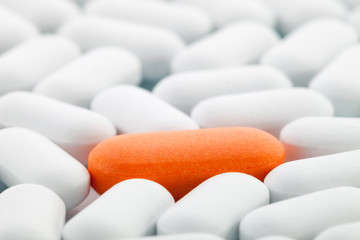 Orange pill between white ones