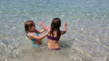 little girls playing in beach water in ibiza island