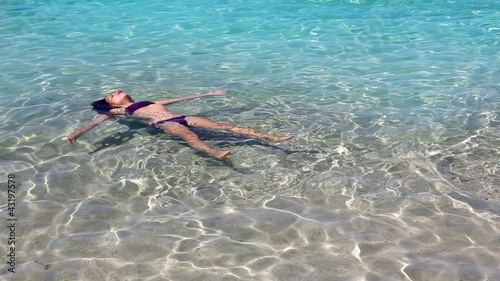 little girl playing and floating in beach water in ibiza island