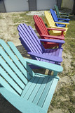 Rainbow colored wooden chairs, known as Maine Chairs, standing in a row outside on the Eastern Shore, Maryland