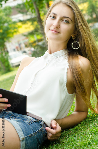 Woman using electronic tablet laying in grass