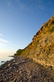 Sunny cliff steep at a stony coast