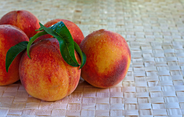 Juicy ripe peaches on raffia background