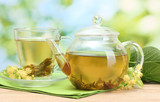 Fototapety teapot and cup with linden tea and flowers