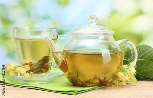 Fototapeta teapot and cup with linden tea and flowers