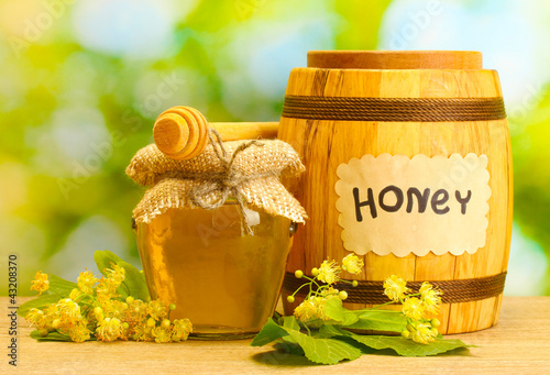 jar and barrel with linden honey and flowers