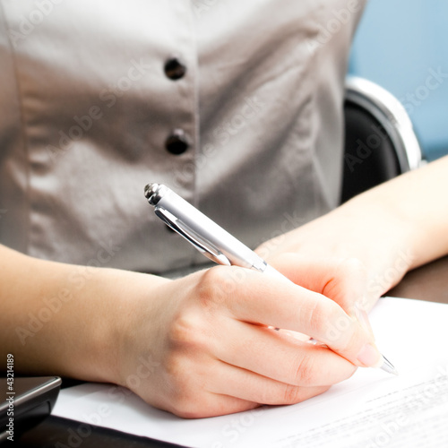 Young business woman writing at office