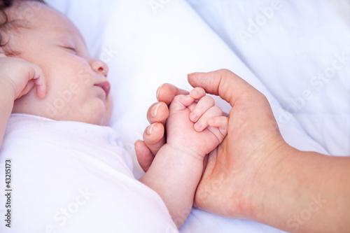 Madre che tiene per mano il bambino che dorme
