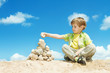 Child putting last stone part to pyramid sitting over sky