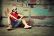 Young man sitting. Grunge graffiti wall