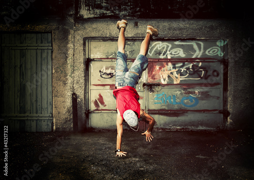 Young man dancing on grunge graffiti wall