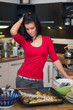 Unhappy woman standing in kitchen
