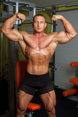 Bodybuilder demonstrating pose in fitness club